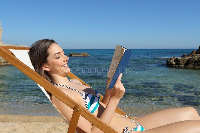 Счастливая женщина читая книгу на пляже на каникулах стоковая фотография
