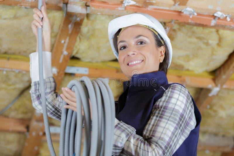 Счастливая женщина-электрик, устанавливающая трубы стоковая фотография