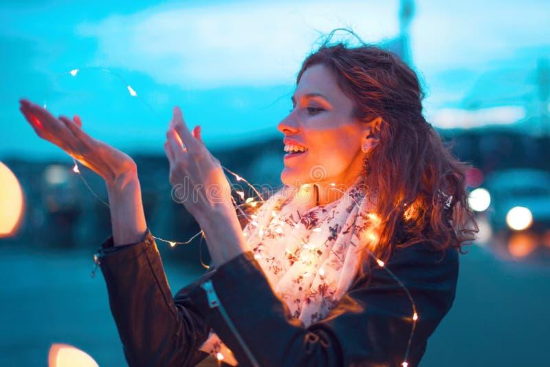 Счастливая женщина redhead держа гирлянду fairy света на вечере стоковая фотография