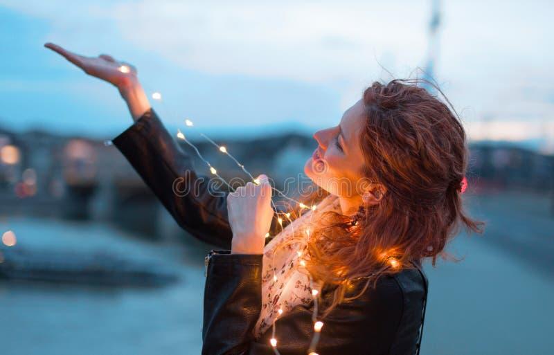 Счастливая женщина redhead с гирляндой fairy света на выравниваться outdoors стоковые изображения