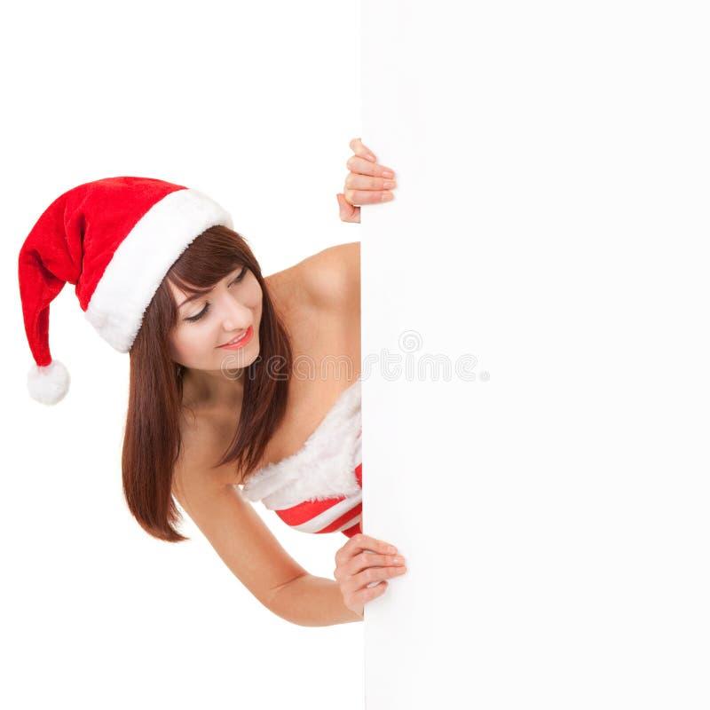 Счастливая женщина santa с белой пустой доской на белизне Модель в шляпе santa на студии держа плакат бумаги стоковое изображение rf
