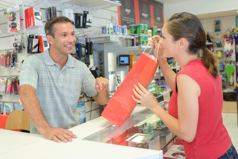 Счастливая женщина tanding с сумками в магазине с сумками стоковые фото