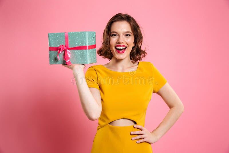 Счастливая женщина ypung с рукой на ее талии держа подарочную коробку, взгляд стоковое изображение