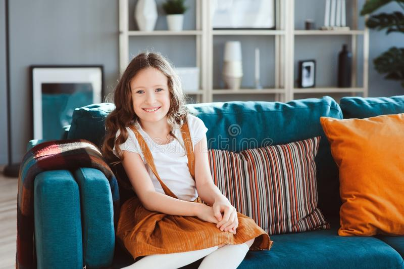счастливая жизнерадостная девушка ребенк представляя с подушкой, уютным креслом позади в современной живущей комнате стоковые фото