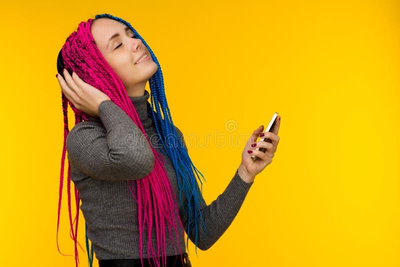 Счастливая жизнерадостная женщина с сенегальскими оплетками и веснушками нося беспроводные наушники слушая музыку от смартфона стоковые фотографии rf