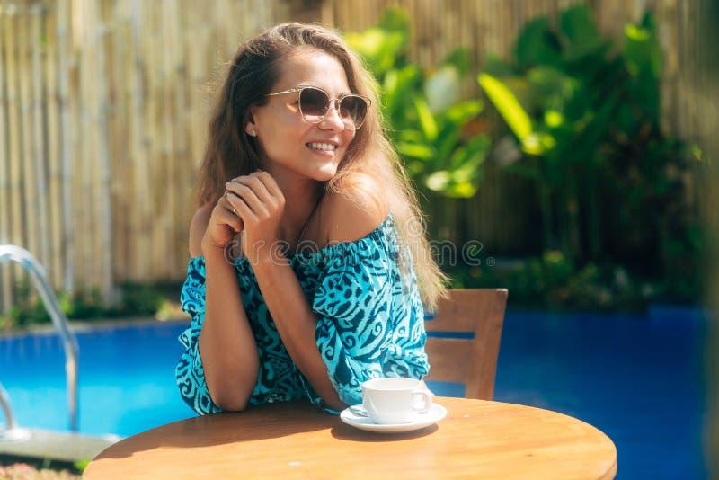 Счастливая загоренная девушка в солнечных очках сидит outdoors на таблице с чашками кофе или чаем стоковое изображение rf