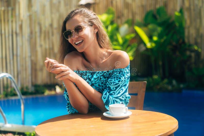 Счастливая загоренная девушка в солнечных очках сидит outdoors на таблице с чашками кофе или чаем стоковое изображение