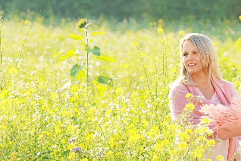 Счастливая зрелая женщина в flowerfield стоковая фотография rf