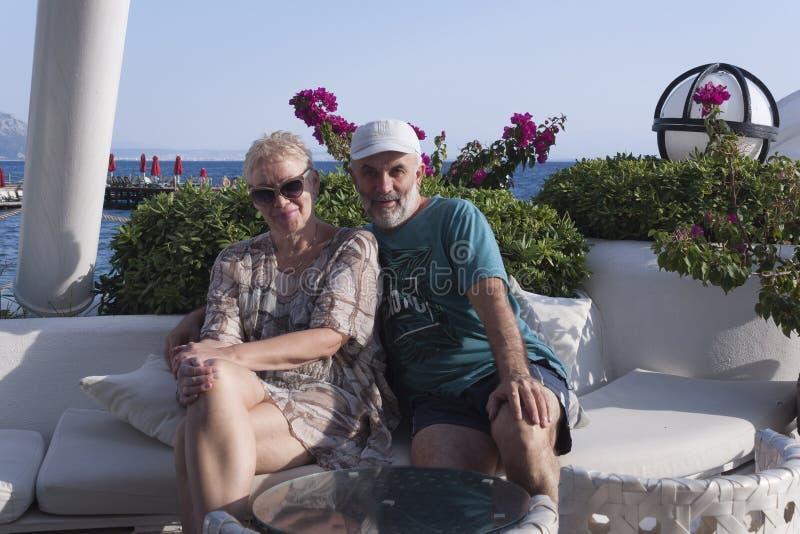 счастливая зрелая пара в отпуске улыбается, сидя на фоне розовых цветов и моря стоковые изображения