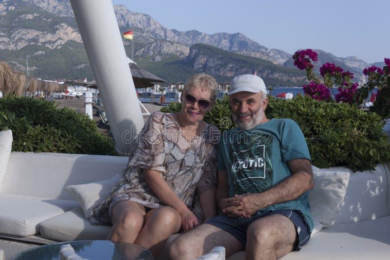 счастливая зрелая пара в отпуске улыбается, сидя на фоне розовых цветов и моря стоковые фотографии rf