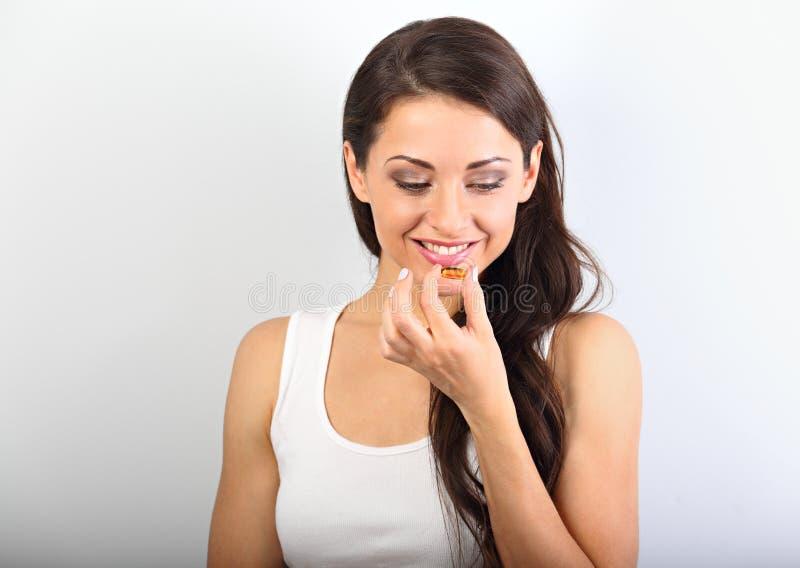Счастливая зубастая усмехаясь женщина принимая таблетку масла трески omega-3 Natur стоковое фото