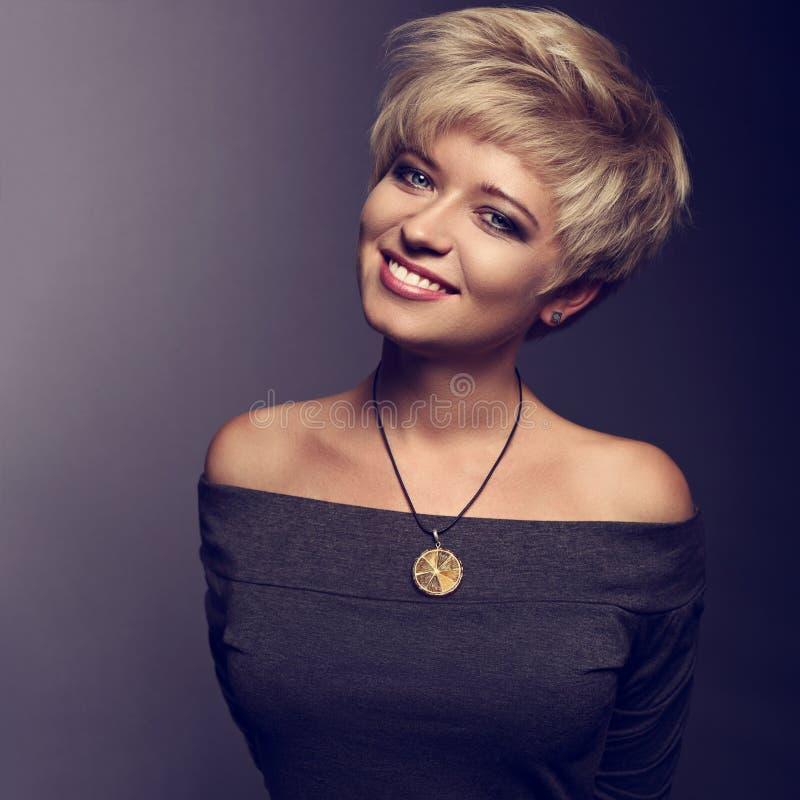 Счастливая зубастая усмехаясь женщина с коротким белокурым стилем причёсок bob в gre стоковые фото