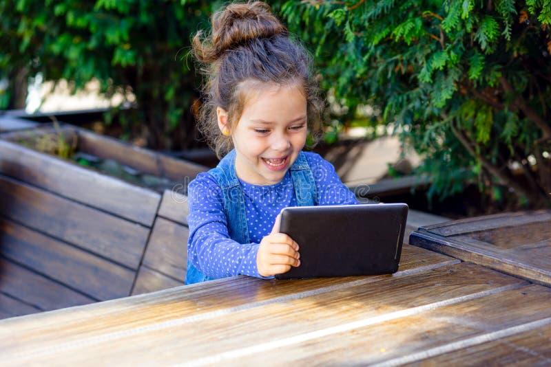 Счастливая игра маленькой девочки в планшете outdoors в кафе Работая выходы стоковые фотографии rf