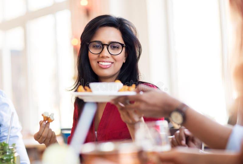 Счастливая индийская женщина есть на ресторане стоковое изображение rf