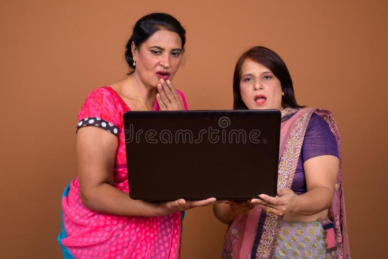 Счастливая индийская женщина 2 используя ноутбук и смотрящ сотрясенный и удивленный стоковая фотография rf
