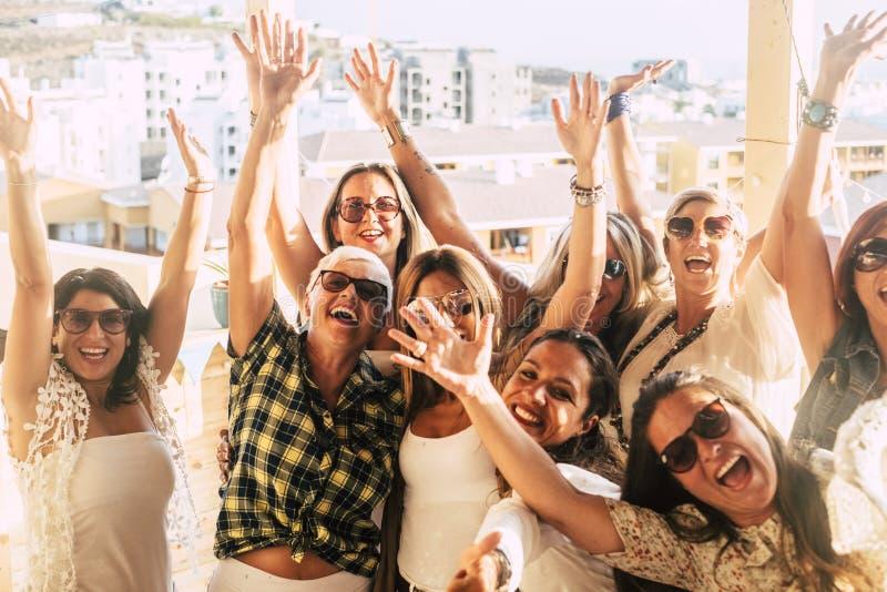 Счастливая и веселая группа женщин-друзей вместе танцуют и веселятся на крыше дома - люди празднуют вместе стоковое фото