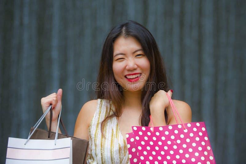 Счастливая и красивая азиатская корейская женщина идя на улицу представляя на хозяйственных сумках нося предпосылки усмехаясь жиз стоковое изображение