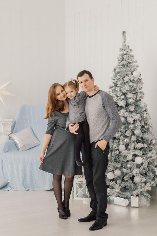 Счастливая и красивая семья из трех человек на комнате праздничной яркого Нового Года стоковое изображение rf
