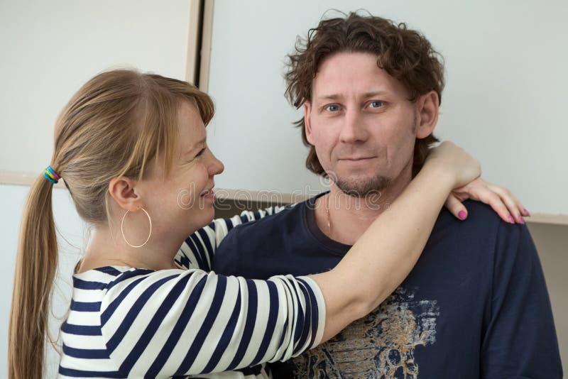 Счастливая и усмехаясь белокурая женщина обнимая ее спокойного человека, крытого стоковые фото