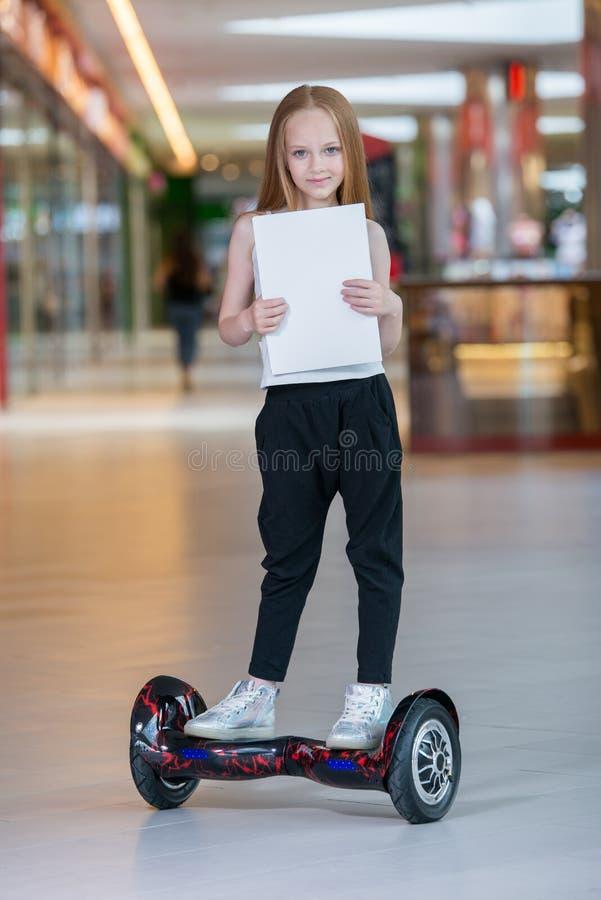 Счастливая и усмехаясь девушка едет на мини segway на торгуя моле Катание подростка дальше завишет чистый лист доски или gyroscoo стоковое фото