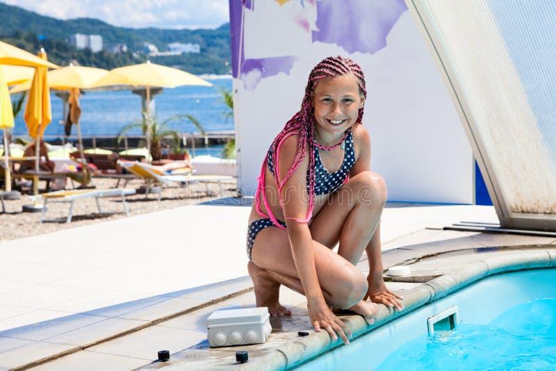 Счастливая и усмехаясь маленькая девочка готовая для того чтобы поскакать в бассейн, розовый dreadlock, загоренную кожу стоковые изображения rf