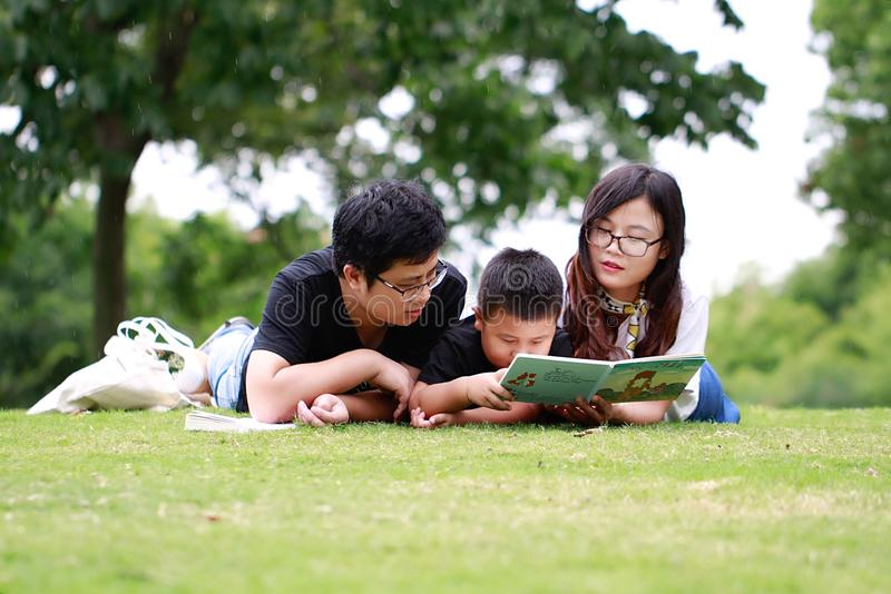 Счастливая книга чтения семьи латиноамериканца стоковые изображения