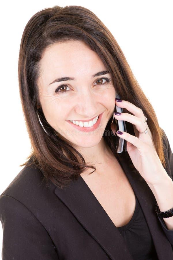Счастливая коммерсантка вызывая на мобильном телефоне усмехаясь в белой предпосылке офиса стоковое фото rf
