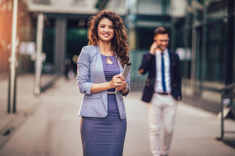Счастливая коммерсантка держа цифровой планшет вне современного здания, бизнесмена в предпосылке стоковое фото