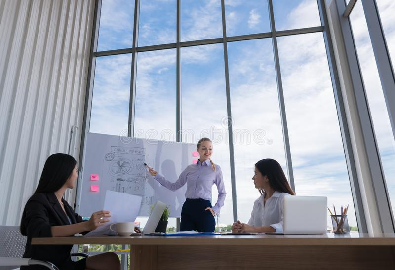 Счастливая коммерсантка имея деловую встречу с его штатом показывать представление на диаграмме сальто или магнитном столе стоковая фотография