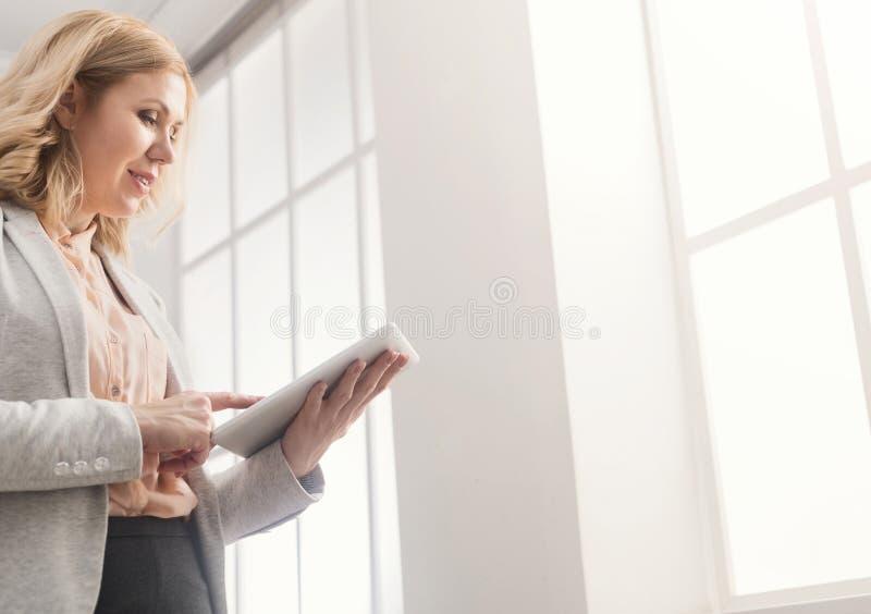 Счастливая коммерсантка на работе используя цифровую таблетку стоковое изображение