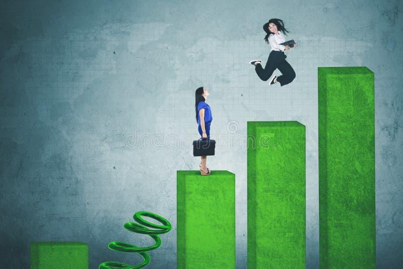 Счастливая коммерсантка скача над ее соперником стоковое изображение