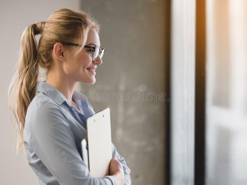 Счастливая коммерсантка стоя около стеклянной стены с бумагами стоковое изображение rf