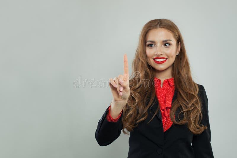 Счастливая коммерсантка указывая ее палец для того чтобы опорожнить космос экземпляра на серой предпосылке знамени стоковая фотография