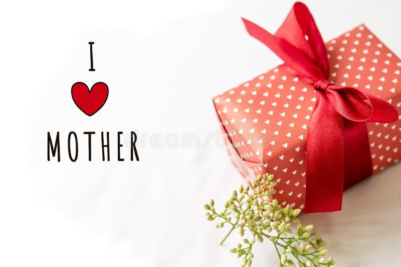 Счастливая концепция дня ` s матери Подарочная коробка и цветок, бумажная бирка с текстом МАТЕРИ ВЛЮБЛЕННОСТИ I стоковое фото
