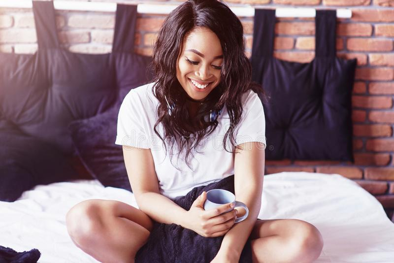 Счастливая красивая африканская девушка в sleepwear протягивая усмехаясь усаживание на кровати дома проспала вверх в утре на солн стоковая фотография