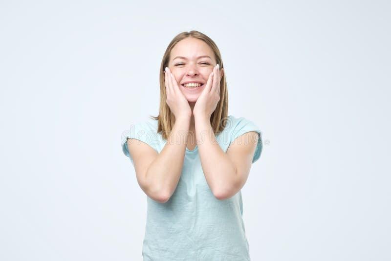 Счастливая красивая девушка держа ее щеки со смехом как говоря я люблю мою кожу Выразительные выражения лица стоковая фотография rf