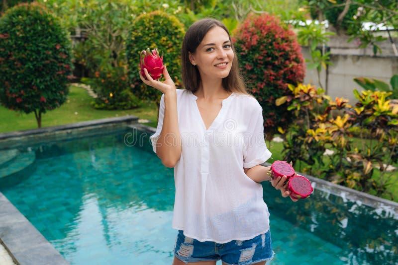 Счастливая красивая девушка держит 2 плода дракона, pitaya в ее руках, бассейн на предпосылке стоковые изображения rf