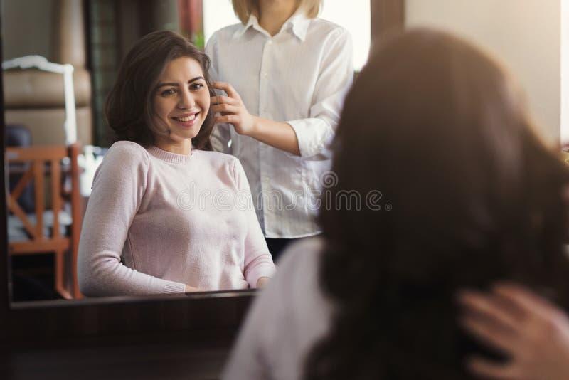 Счастливая красивая женщина обсуждая стиль причёсок с ее парикмахером стоковая фотография
