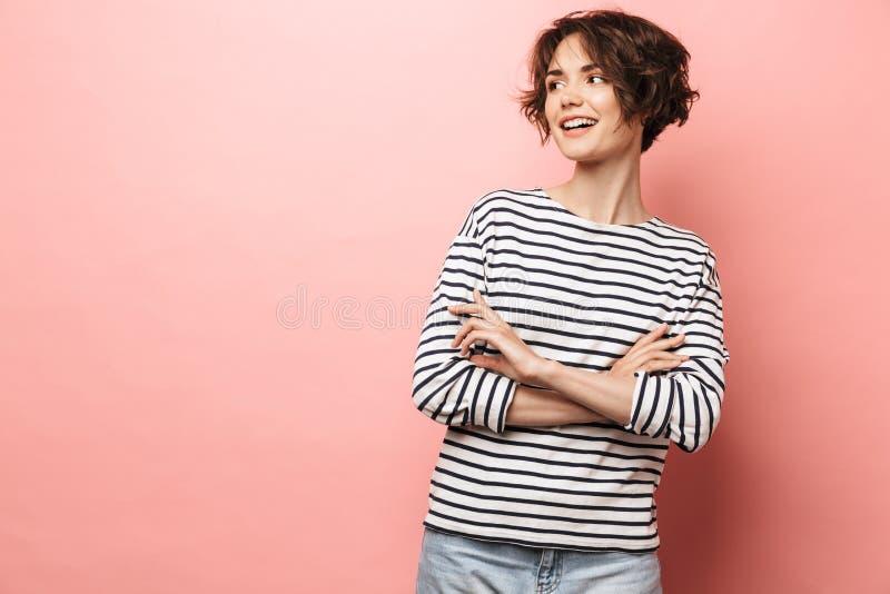 Счастливая красивая женщина представляя над розовой предпосылкой стены стоковое фото rf