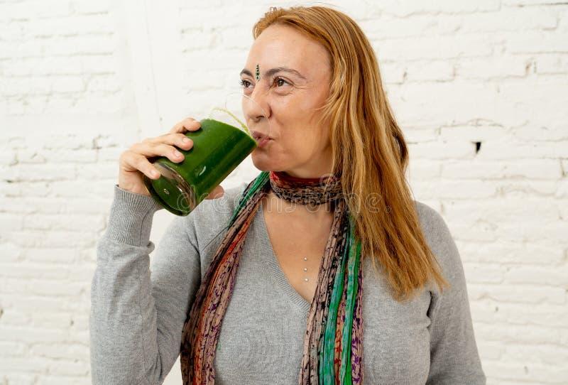 Счастливая красивая женщина усмехаясь и выпивая здоровый smoothie свежего овоща в здоровом образе жизни стоковые фото