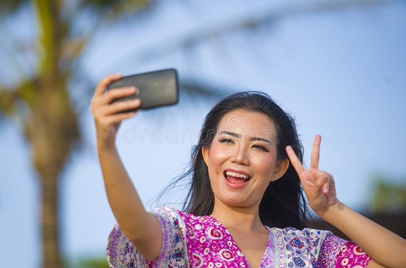 Счастливая красивая и шикарная азиатская китайская женщина в платье очарования принимая фото selfie автопортрета с мобильным теле стоковая фотография
