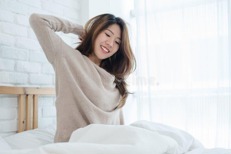 Счастливая красивая молодая азиатская женщина просыпая вверх в утре, сидящ на кровати, протягивающ в уютной спальне, смотря через стоковые изображения