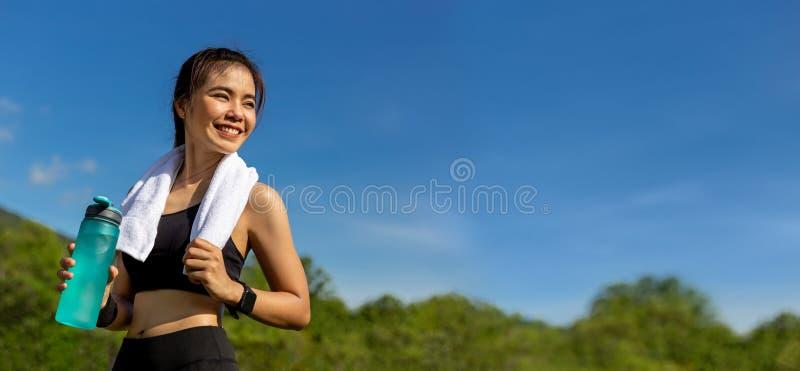 Счастливая красивая молодая азиатская женщина с ее белым полотенцем над ее шеей, положение усмехаясь и держа ее бутылку с водой д стоковое изображение
