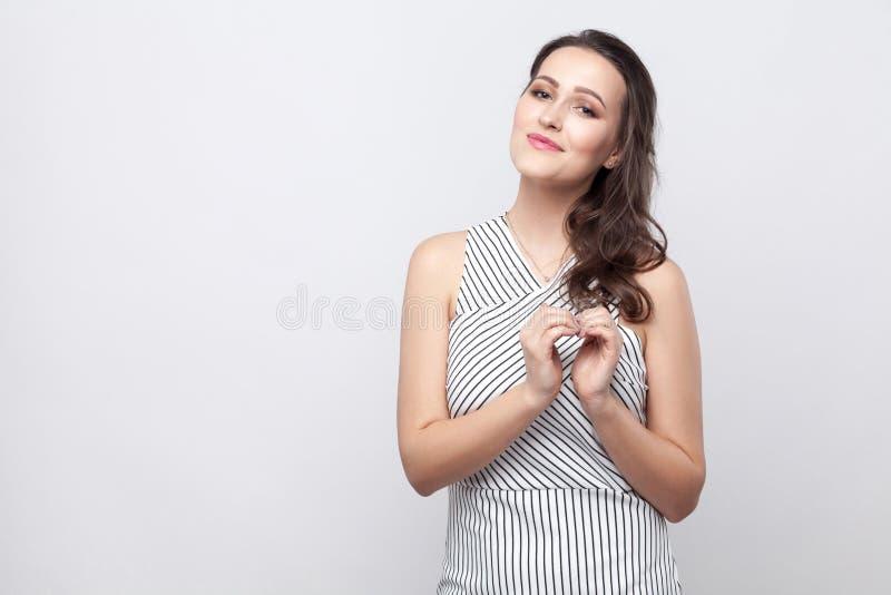 Счастливая красивая молодая женщина брюнета с макияжем и striped положением платья, на камере с улыбкой и добротой и сердцем пока стоковые изображения
