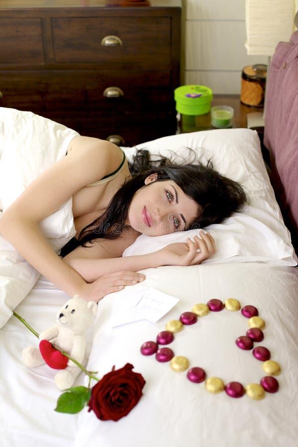 Счастливая красивейшая женщина в кровати с романтичными подарками от парня стоковое фото rf