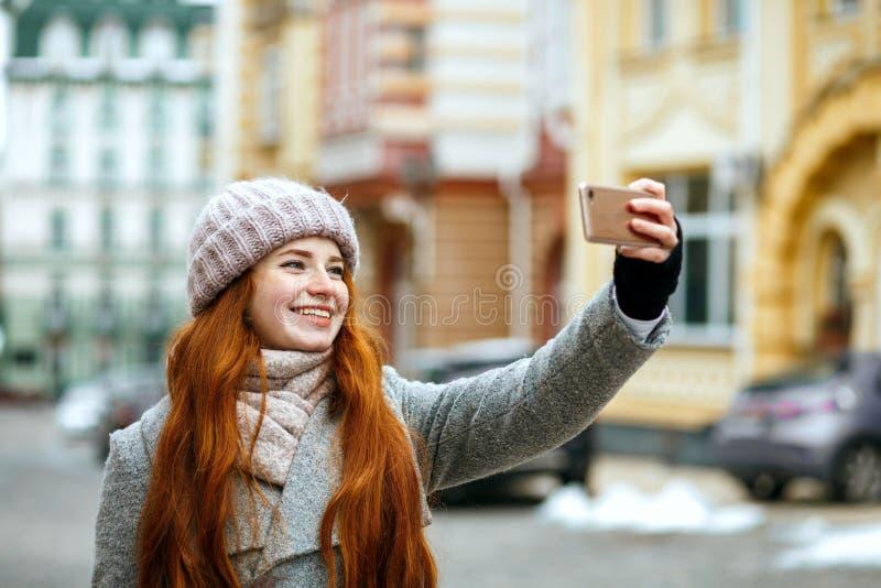 Счастливая красная главная женщина в одеянии зимы принимая selfie на ее mobi стоковые фотографии rf