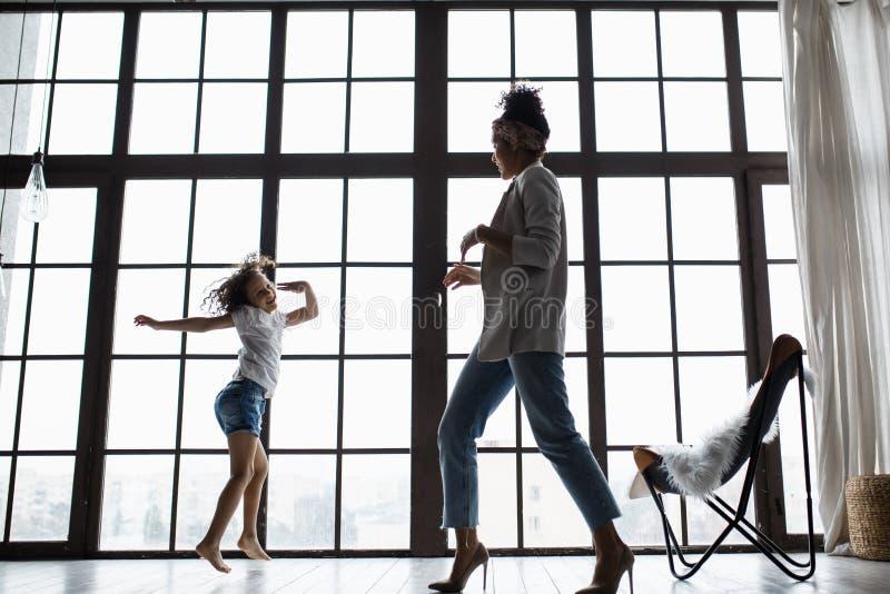 Счастливая любящая афро американская семья Молодая мать и ее дочь играя в питомнике Мама и дочь танцуют на стоковое изображение rf