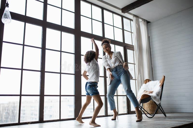 Счастливая любящая афро американская семья Молодая мать и ее дочь играя в питомнике Мама и дочь танцуют на стоковое фото rf