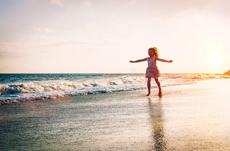 Счастливая маленькая девочка бежать внутри воды распространяя ее руки вверх на пляже - младенце имея потеху делая брызгать в море стоковые изображения rf