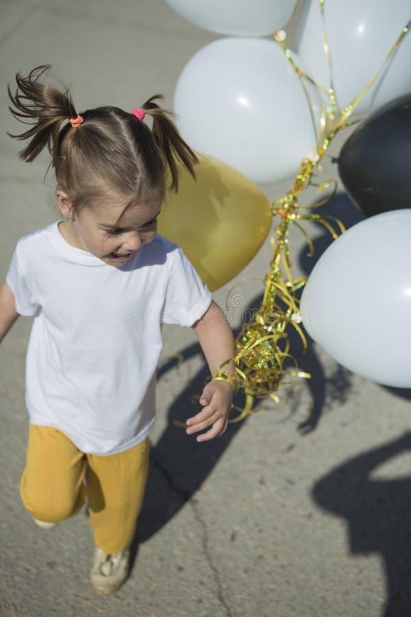 Счастливая маленькая девочка бежать с воздушными шарами стоковое фото rf